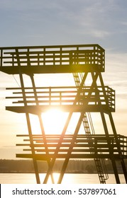 Tower for swimmers on a sunset. Jump to dive in three heights on a lake shore.