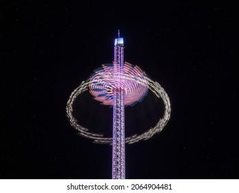 Tower Swinger Ride In Amusement Park at night at anual funfair