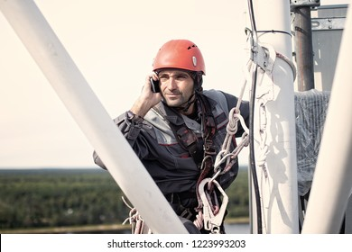 tower technician talking on a cell phone on a telecommunications tower. the concept of checking cellular signal. Copy space for your text