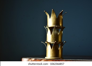 Tower of three shiny brass crowns.