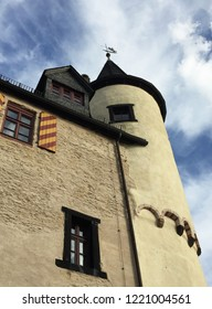 A tower with a turret is seen rising into a blue sky with white clouds. A weather vane is on the turret.  Windows are in the wall of the castle, one with red and yellow striped shutters.