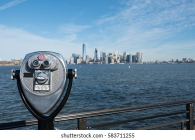 Tower viewer telescope looking at lower Manhattan skyline from Liberty Island. Railing and binoculars on a stand for tourists to view New York City from across the New York Harbor.