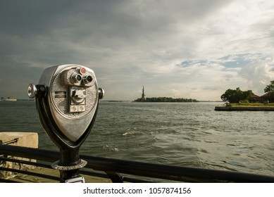 Tower viewer/Abstract image of a coin operated public telescope binoculars on the bay shore across from the Statue of Liberty and Ellis Island in New York City.