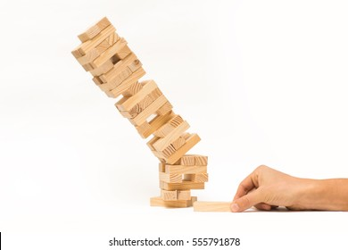 Tower of wooden blocks and man's hand take one block. Isolated tower collapses on white background.