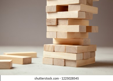 Tower of wooden blocks on gray background. Board game for the whole family or party. Concept of building business or building team. Copy space for text