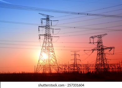 Towering high voltage power tower in the sunset