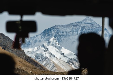 The towering peak of Mount Everest looms through the bus window as these travelers approach the mountain.