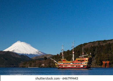 The towering snow-capped Mt. Fuji, the pirate ship and a gate of the Hakone shrine seen on a clear winter morning from the Moto-Hakone port on Lake Ashi in Kanagawa prefecture.