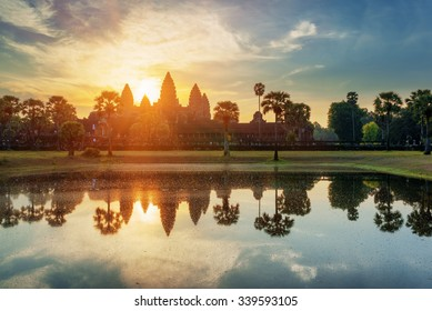 Towers of ancient temple complex Angkor Wat at sunrise. Siem Reap, Cambodia. Temple Mountain and the sun reflected in lake at dawn. Mysterious Angkor Wat is a popular tourist attraction.
