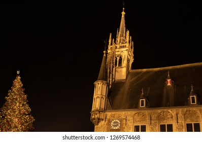 Towers of the ancient town hall of Gouda, The Netherlands, with the top of a huge decorated Christmas tree in the night.