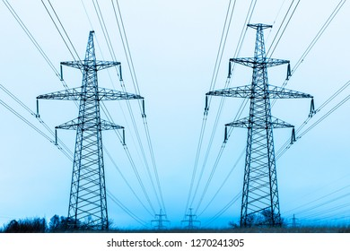 Towers of electric main in the winter snowy countryside field on the background of blue sky and the forest with the wires