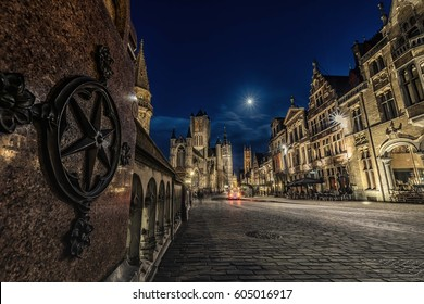 The towers of Gent in the evening with shining moon in the dark blue sky