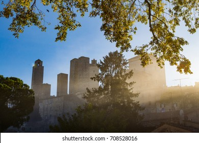 the towers of the old village San Gimignano in Italy, seen through the leaves of an old beautiful tree