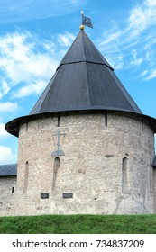 Towers and walls of the fortress of Holy Dormition Pskov-Caves Monastery in Pechory, Russia. Izborsk Tower with decorative weathervane and cross on wall.