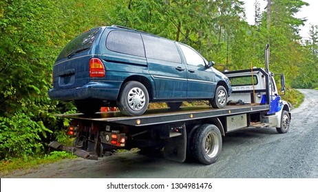 Towing service - the blue tow truck with the loaded old damaged car which stopped working in the middle of forest on the rough off road. Back view