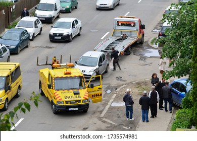 Towing service is moving a damaged peugeot to a flatbed tow truck after a car crash on the street in Cluj-Napoca, Romania, on May 28, 2015. Another blue car drove up the sidewalk into the hedge.