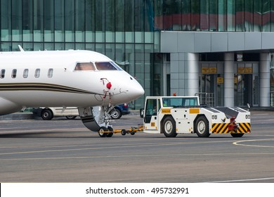 Towing truck pushing back the small private business jet to the parking place at the airport