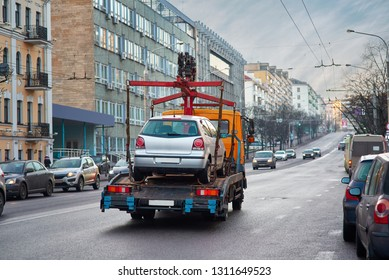 Towing of vehicle on forklift truck. Tow truck with equipped hydraulic manipulator for emergency car move driving along the road. Parking in violation of traffic rules problem. Сar accident concept