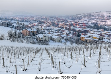 Town of Alba among hills and vineyards covered with snow in Piedmont, Northern Italy.