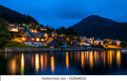 Town Balestrand in Norway during nights with houses and light reflections