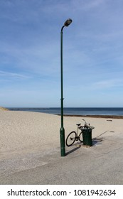 Town bicycle leaning against a metal bin with lampost, beach and blue winter sky