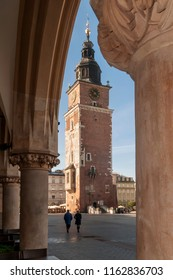 The town hall tower framed by the central market columns of Krakow, Poland