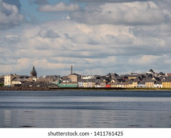 Town landscape, Galway, Ireland, Claddagh area, Colorful houses, blue ocean water, cloudy sky.