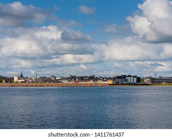 Town landscape, Galway, Ireland, port and Claddagh area, Colorful houses, blue ocean water, cloudy sky.