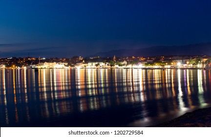Town of Novalja at night and light reflections in the water, Croatia, Adriatic sea, Europe