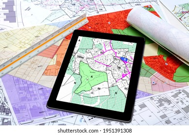Town Planning and Land Use - digital tablet displaying a land use plan, placed on French maps of local town planning