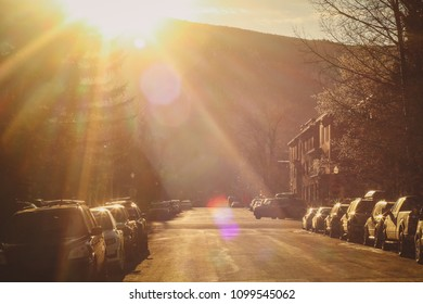 A town road in Aspen, Colorado during the late afternoon in the spring. Sun just setting behind the hill, producing a nice lensflare and silhouette of traffic and parked cars.