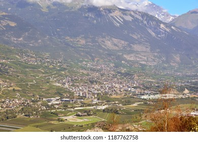 The town of Sierre in the canton of Valais, southern Switzerland with the River Rhone flowing in the foreground and the Bernese Alps behind