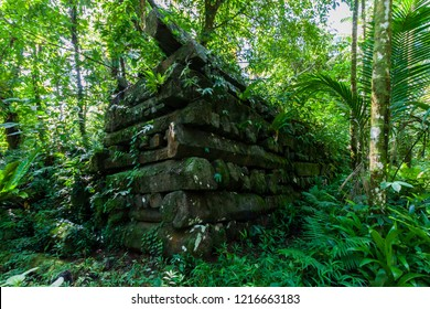 Town walls overgrown in jungle, Nan Madol - prehistoric ruined stone city built of basalt slabs. Ancient walls were built on coral artificial islands in the lagoon of Pohnpei, Micronesia, Oceania.