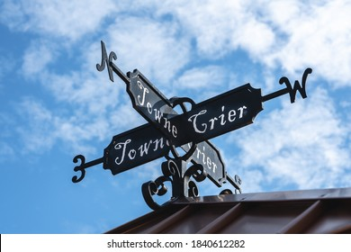 towne crier weathervane sign on the roof of a building with a partly cloudy blue sky