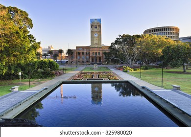 town-hall of the city of Newcastle behind still pool in a park decorated by blooming flowers at sunrise