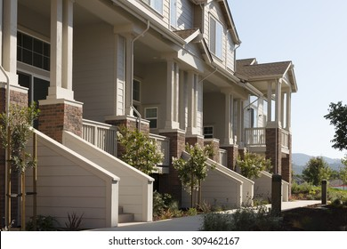 Townhome porches along a common walkway.