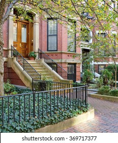 Townhouse apartments in Back Bay, Boston. Brick row houses and sidewalk, cast-iron fence and railings, stone steps, bay windows, garden urns…