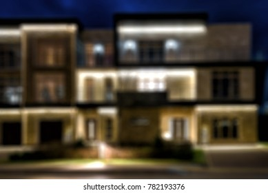 Townhouses in the night town, creative abstract blur background with bokeh effect. Lighting of house at dusk.