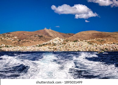 Towns of Ermoupolis and Ano Syros in the Greek island of Syros, Cyclades, viewed from a departing speed boat
