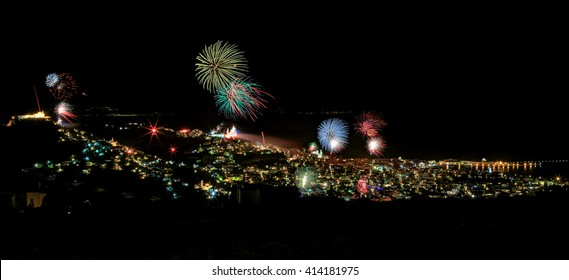 Towns of Ermoupolis and Ano Syros on the Greek island of Syros, Cyclades, with fireworks in the night of resurrection, in Greek Easter