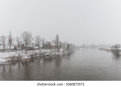 Townscape of Nienburg in fog and snowfall in winter with steeple, houses, Weserwall and Weser seen from the pedestrian bridge