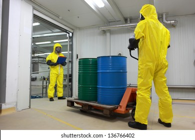 toxic substance delivering - Two specialists in protective uniforms,masks,gloves and boots, dealing with barrels of toxic substance on forklift in factory