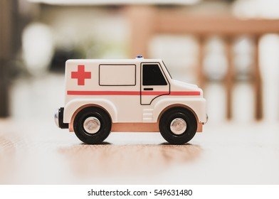Toy ambulance car with a red cross on wooden table in soft focus