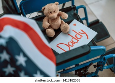 Toy, American flag and paper with inscription Daddy situating in wheelchair. Homecoming and military concept
