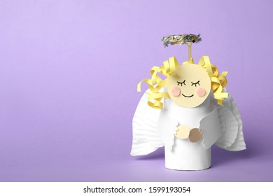 Toy angel made of toilet paper hub on lilac background. Space for text