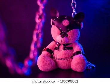 toy bear dressed in leather belts harness accessory for BDSM games on a dark background in neon light