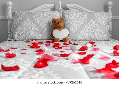 Toy Bear holding a blank heart on bed with red rose petals.