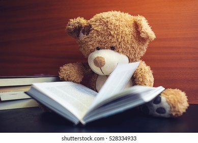 toy bear reading an interesting book, showing that even read toys. the concept of baby learning