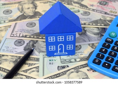 A toy blue house on U.S. Dollar notes with calculator and pen.