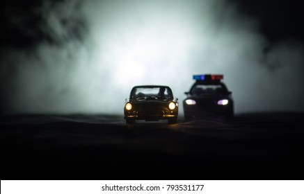 Toy BMW Police car chasing a Ford Thunderbird car at night with fog background. Toy decoration scene on table . Selective focus - 11 JAN 2018, BAKU AZERBAIJAN